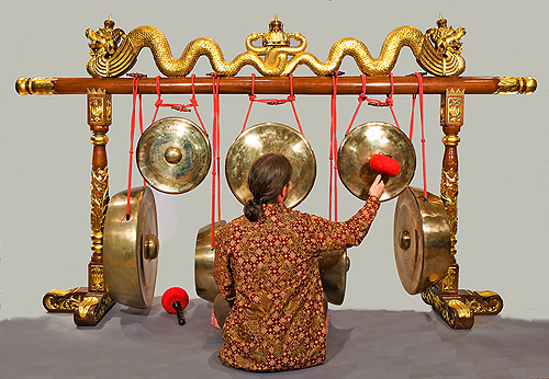 A musician plays one of the gongs in the Kyai Rengga Manis Everist Gamelan