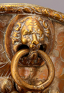 Ring in lion's mouth on brass plate applied to garland